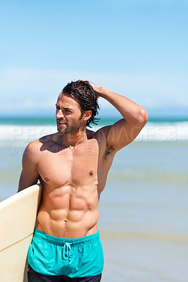 Buy stock photo An attractive young man heading to the water with his surfboard