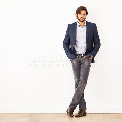 Buy stock photo Portrait of a confident young businessman leaning against a white wall