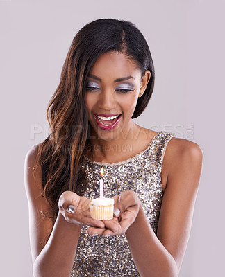 Buy stock photo Studio shot of a gorgeous  young woman holding a cupcake and candle against a gray background