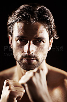 Buy stock photo Portrait of a muscular young boxer standing ready to fight