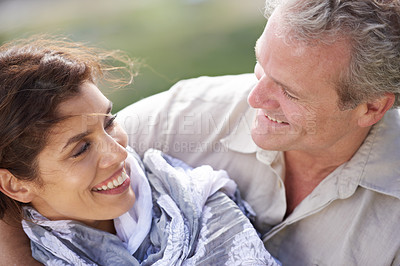 Buy stock photo Shot of a mature couple laughing and embracing while enjoying a day out in nature