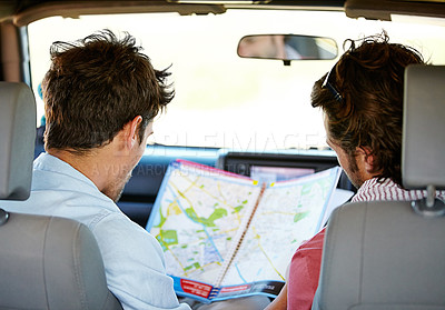 Buy stock photo Two friends consulting a road map
