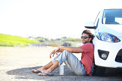 Buy stock photo A young man sitting on the road against the wheel of his car