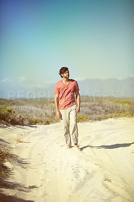Buy stock photo A young man walking along a deserted road