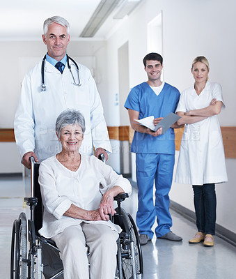 Buy stock photo Shot of a senior woman in a wheelchair with medical professionals in the background