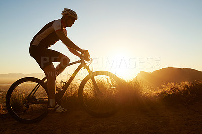 Buy stock photo Full length shot of a man cycling in the mountains