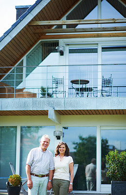 Buy stock photo Cropped portrait of a mature couple standing hand-in-hand in front of their home