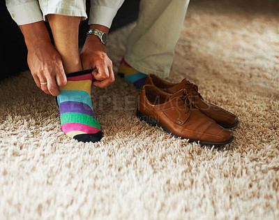 Buy stock photo Cropped shot of a man putting on colourful socks and loafers