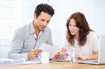 Buy stock photo Shot of two colleagues discussing paperwork while sitting with a laptop