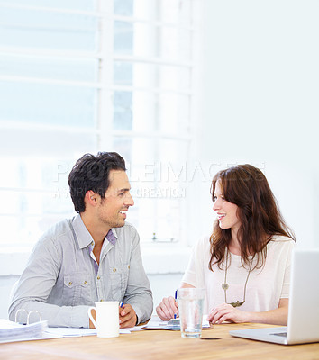 Buy stock photo Shot of two colleagues having a friendly conversation while working together