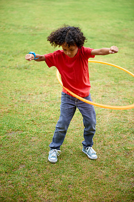 Buy stock photo Full length shot of a young boy hula hooping outdoors