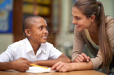 Buy stock photo Shot of a teacher helping her student with his work in the classroom