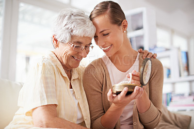 Buy stock photo Cropped shot of a senior woman giving her daughter a pearl necklace