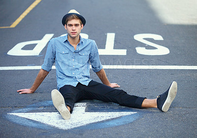 Buy stock photo Portrait of a handsome hipster sitting in the middle of the street