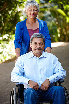 Buy stock photo Portrait of a senior woman pushing her husband in a wheelchair outdoors