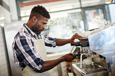 Buy stock photo Shot of a handsome male barista making a cup of coffee using an espresso machine