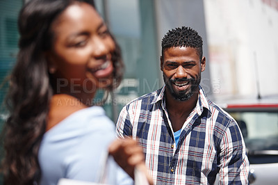 Buy stock photo Shot of a handsome man posing with his girlfriend in the foreground