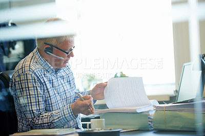 Buy stock photo A senior businessman wearing a headset discussing paperwork over the phone