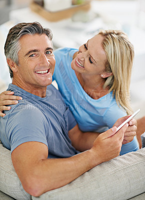 Buy stock photo Portrait of a laughing couple sitting at home using a digital tablet