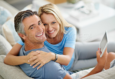 Buy stock photo Portrait of a smiling couple sitting at home using a digital tablet