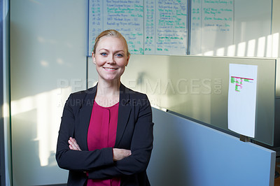 Buy stock photo Portrait of an attractive businesswoman standing with her arms crossed in the office