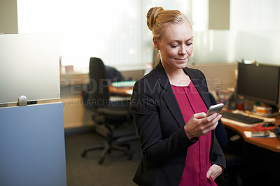 Buy stock photo Cropped shot of an attractive businesswoman using he cellphone in the office
