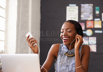 Buy stock photo Shot of a young designer listening to music on her phone while working on her laptop