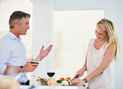 Buy stock photo Shot of a mature couple talking together while making dinner