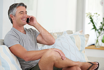 Buy stock photo Shot of a handsome mature man talking on the phone while relaxing at home