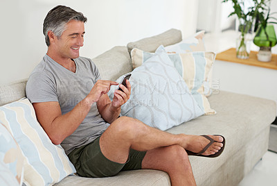 Buy stock photo Shot of a handsome mature man using his phone while relaxing at home