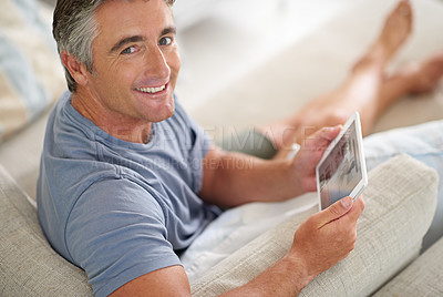 Buy stock photo Portrait of a handsome mature man using a digital tablet while relaxing at home