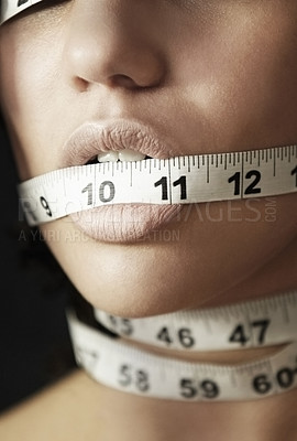 Buy stock photo Concept shot of an anorexic woman with measuring tape wrapped around her head