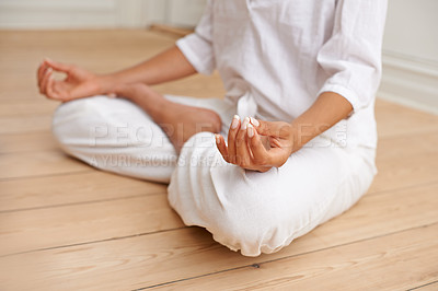 Buy stock photo Cropped shot of a woman sitting in the lotus position during a yoga session