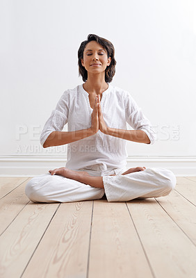 Buy stock photo Shot of a beautiful young woman sitting in the lotus position during a yoga session