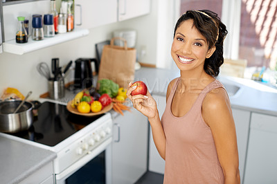 Buy stock photo Portrait of a young woman standing in a kitchen