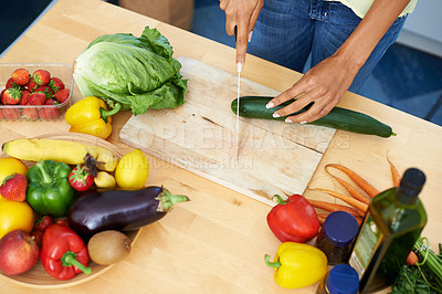 Buy stock photo Cropped shot of a young woman slicing vegetables in a kitchen