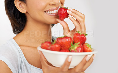 Buy stock photo Cropped shot of a young woman enjoying a bowl of strawberries