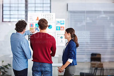 Buy stock photo Rearview shot of creative professionals working together on designs