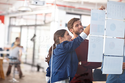 Buy stock photo Cropped shot of two creative professionals working together at a glass wall with designs on it