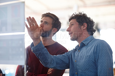 Buy stock photo Two creative professionals working together at a glass wall with designs on it