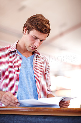 Buy stock photo Cropped shot of a handsome young businessman looking over some paperwork