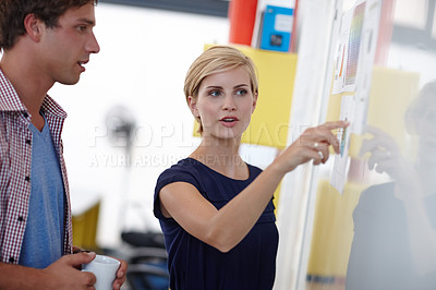 Buy stock photo Cropped shot of a young businesswoman explaining something to her colleague at a whiteboard