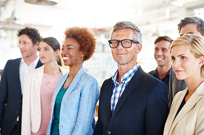 Buy stock photo Cropped portrait of a mature businessman standing amongst his colleagues in the office