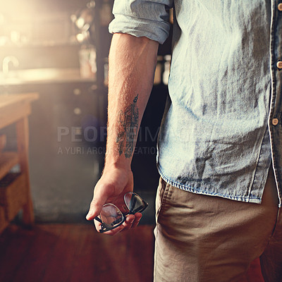 Buy stock photo Cropped shot of a man holding a pair of glasses