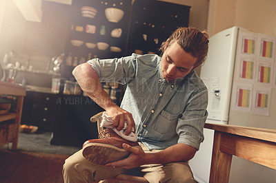 Buy stock photo Cropped shot of a handsome young man cleaning his shoes in the kitchen