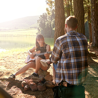 Buy stock photo Shot of a young woman playing guitar for her boyfriend at their campsite
