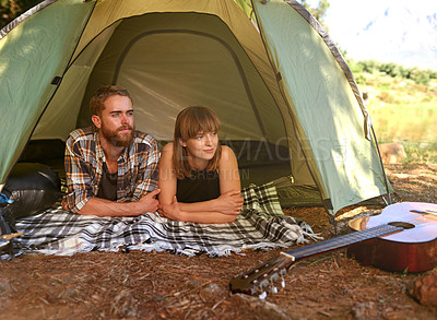 Buy stock photo Shot of a young couple lying in a tent looking outwards