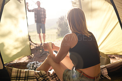 Buy stock photo Shot of a young man watching his girlfriend drinking coffee inside a tent