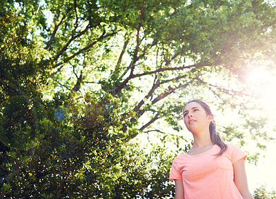 Buy stock photo Shot of a sporty young woman walking beside trees