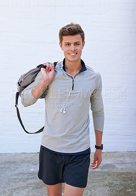 Buy stock photo Shot of a handsome young man holding his gym bag, ready for a workout